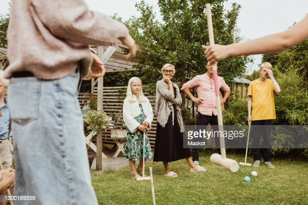 family ready to play polo in back yard of house - polo stock pictures, royalty-free photos & images