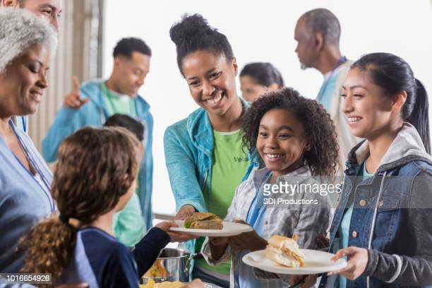 family receives health meal in soup kitchen - homeless shelter stock pictures, royalty-free photos & images