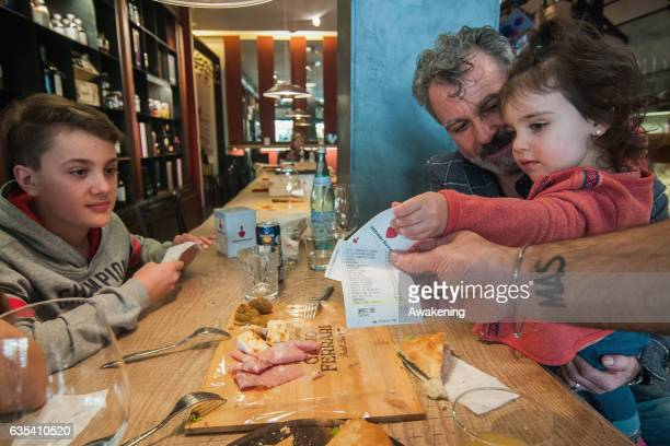 Family receives the bill with the discount of 5% for the good behavior of one child in the Antonio Ferrari restaurant on February 15, 2017 in Padova,...