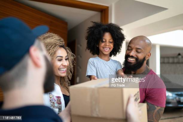 family receiving a delivery from the mailman - receiving stock pictures, royalty-free photos & images