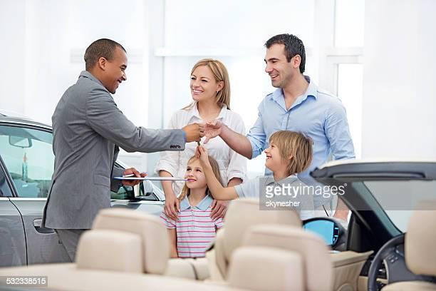 Family receiving a new car keys.