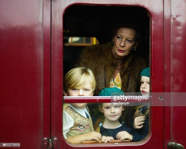 A family reenacting the journey of young war evacuee's look from the window of a railway carriage during the North Yorkshire Moors Railway 1940's...
