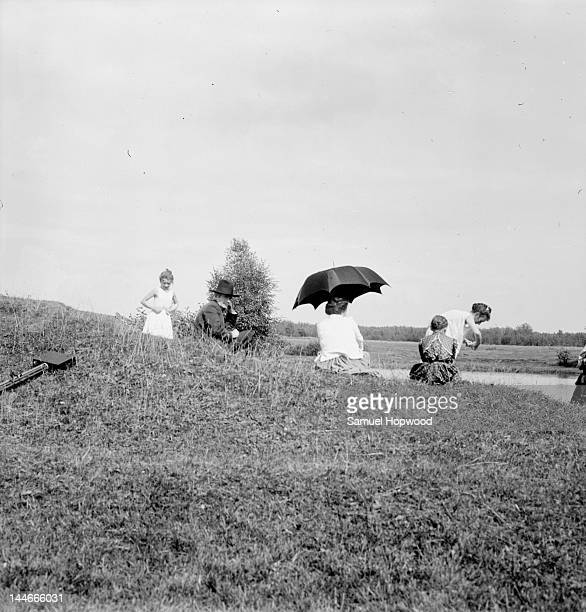 Family relax on sunny river bank woman sits under umbrella man sits in suit and dark hat daughters in slips dry their clothes Russia 1900s