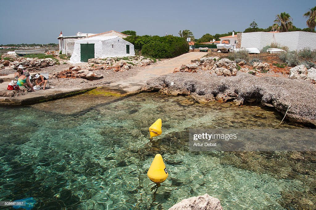 Family relax time in the beach in the Minorca's island wit crystal clear water on summer time. Balearic Islands Europe.