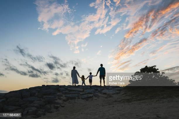 family relaxed in the beach at dusk - anticipation fotografías e imágenes de stock