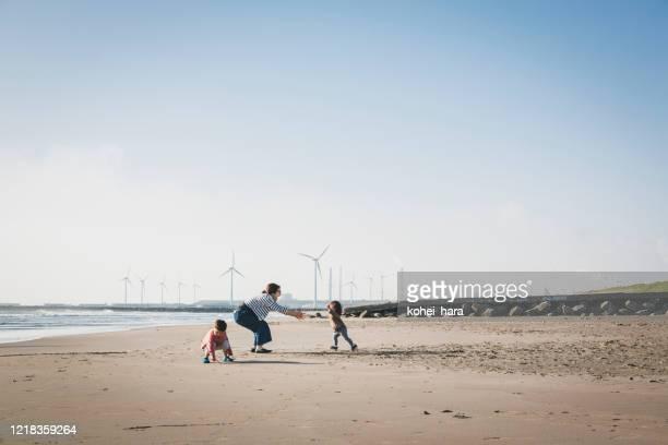 風力発電所に近いビーチでリラックスした家族 - シンプルな暮らし ストックフォトと画像