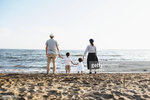 ビーチでリラックスした家族 - 保険 ストックフォトと画像