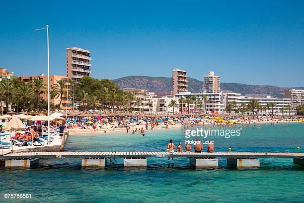 Family relaxes on pier at Playa de Magaluf beach