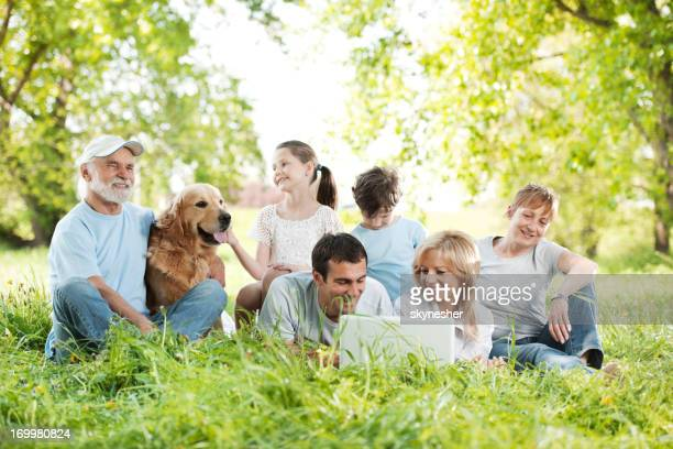 Family relaxing and looking at laptop in the park.