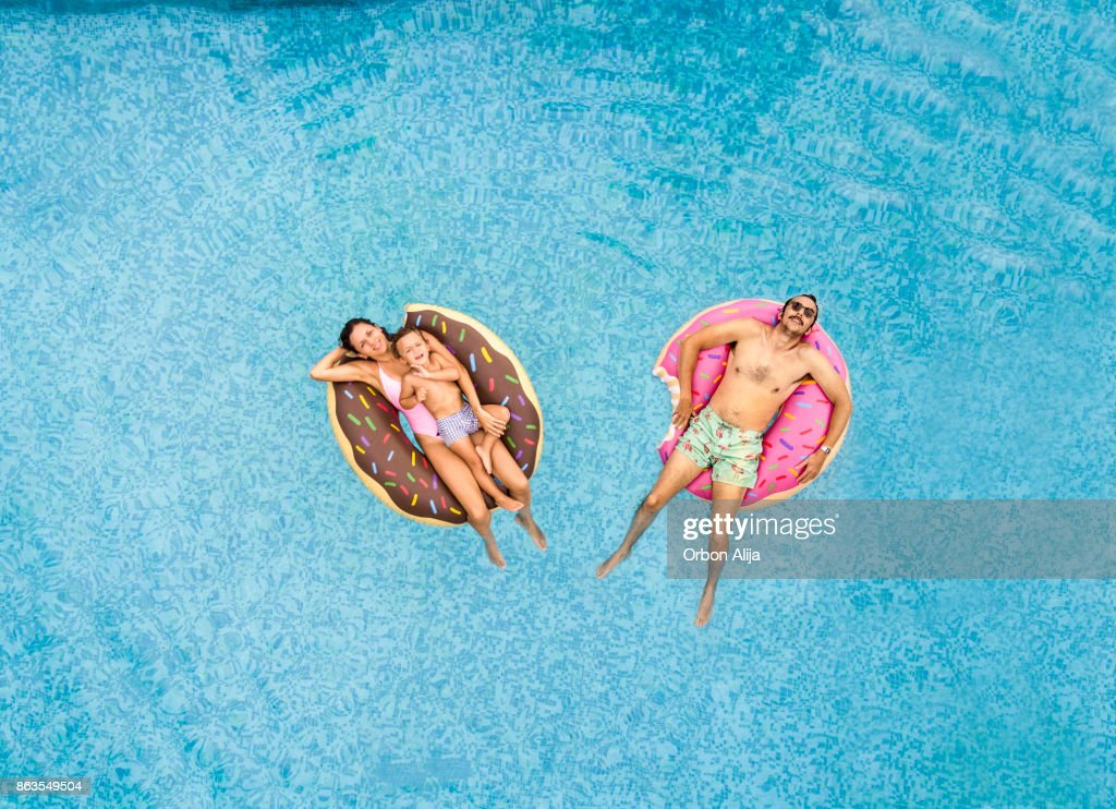 Family relaxing at swimming pool : Stock Photo
