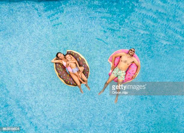 family relaxing at swimming pool - pool stock pictures, royalty-free photos & images