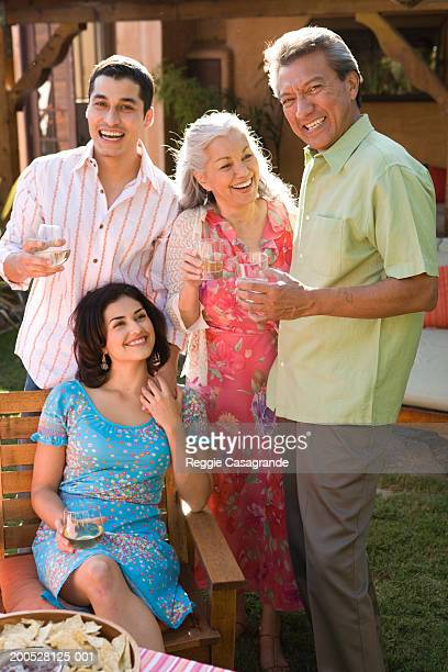 Family relaxing in garden with glass of wine, smiling, portrait