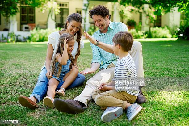 family relaxing in lawn - 30 39 years stock pictures, royalty-free photos & images
