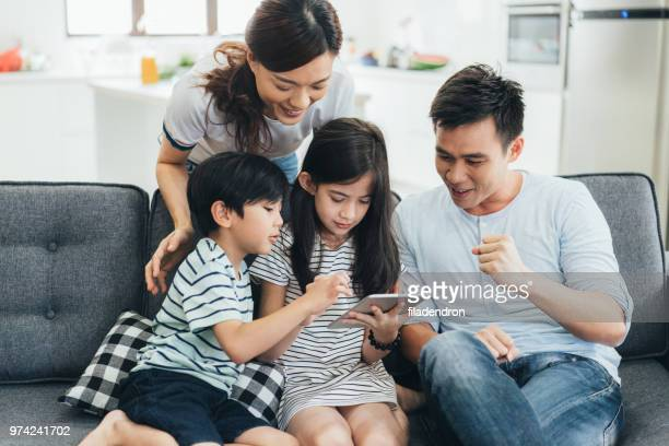family relaxing in the living room with digital tablet - east asian ethnicity stock pictures, royalty-free photos & images