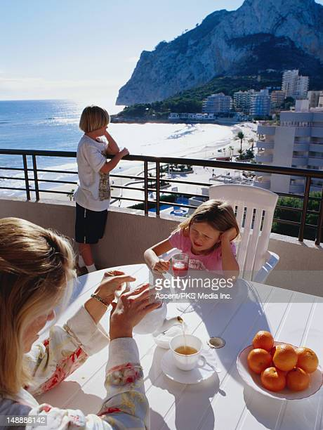 Family relaxing on a balcony overlooking the beach.