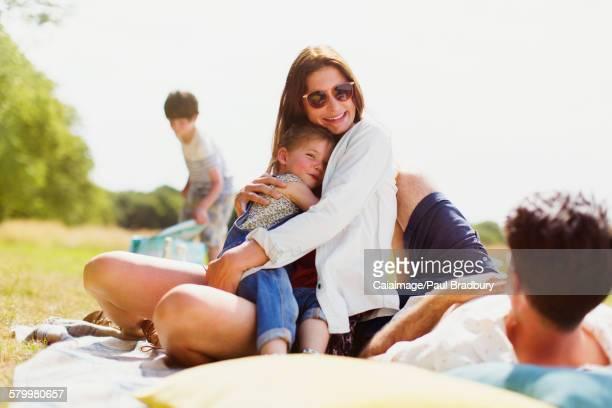 Family relaxing on blanket in sunny field