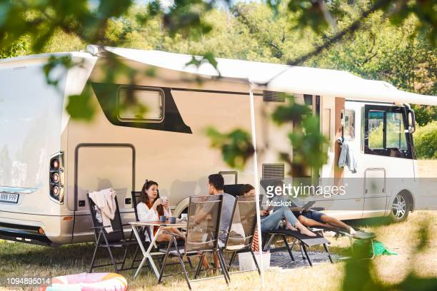 family relaxing on chairs outside camper van at campsite during summer vacation - camper trailer stock pictures, royalty-free photos & images