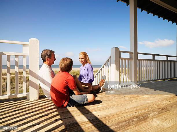 Family Relaxing on Porch of Beach House