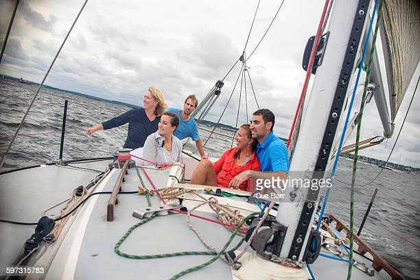 family relaxing on sailboat, looking away smiling - navigation de plaisance photos et images de collection