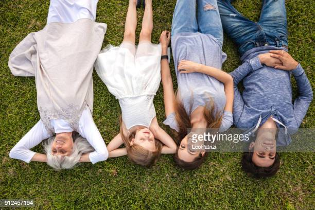 Family relaxing on the grass in the garden