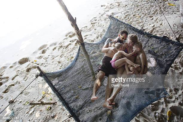 Family relaxing together in hammock.