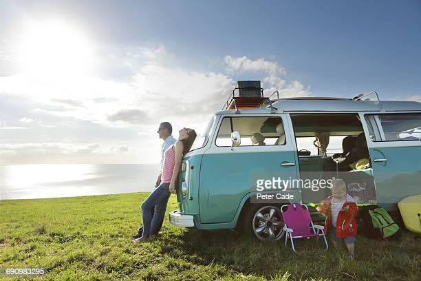 Family relaxing with camper in field by sea