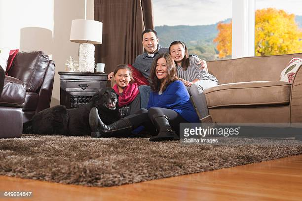 Family relaxing with dog in living room