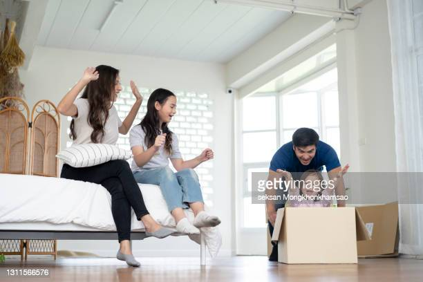 family relocation concept. dad riding little daughter in moving box having fun in new home. - mortgage stock pictures, royalty-free photos & images