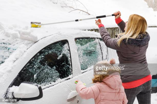 Family removing snow from their car together