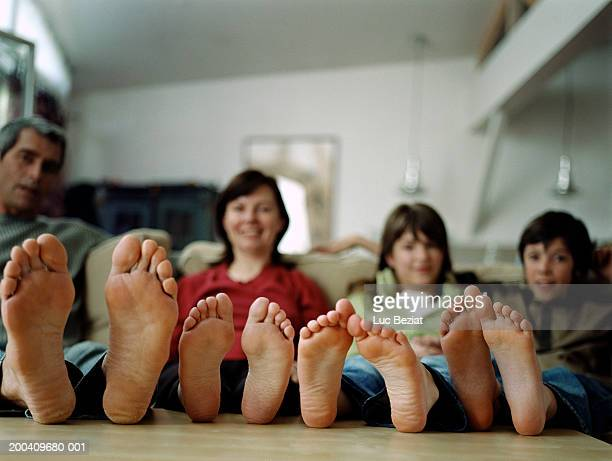 family resting bare feet on coffee table (focus on feet) - male feet soles stock photos and pictures