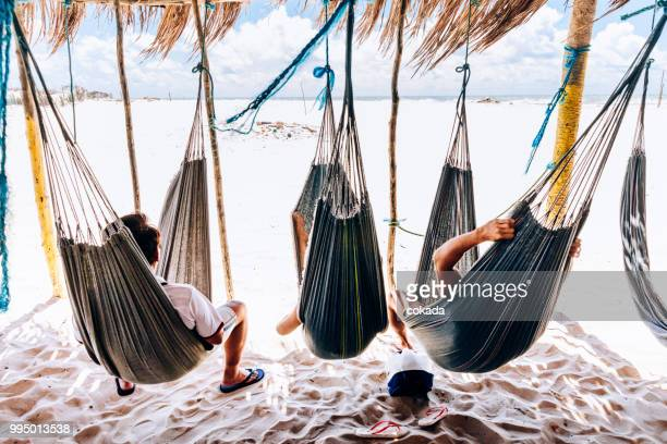 family resting on hammock at lençois maranhenses - maranhao state stock pictures, royalty-free photos & images