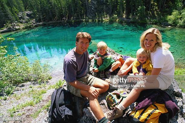 Family resting on rock after hike, lake in background, portrait