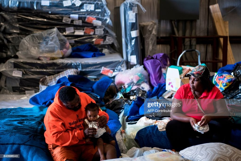 TOPSHOT - A family rests in a shelter at a Gallery Furniture store during the aftermath of Hurricane Harvey on August 30, 2017 in Houston, Texas. Monster storm Harvey made landfall again Wednesday in Louisiana, evoking painful memories of Hurricane Katrina's deadly strike 12 years ago, as time was running out in Texas to find survivors in the raging floodwaters. / AFP PHOTO / Brendan Smialowski