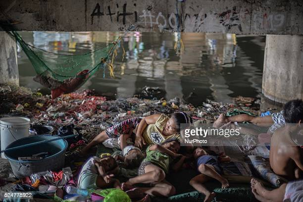 A family rests under a busy bridge they use as a shelter in Paranaque suburban Manila Philippines June 3 2014 Between the water below and traffic...