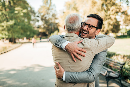 Family reunion. Father and son hugging outdoors. 1055485690