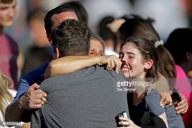 A family reunites outside of Stoneman Douglas High School in Parkland Fla after a shooting on Wednesday Feb 14 2018