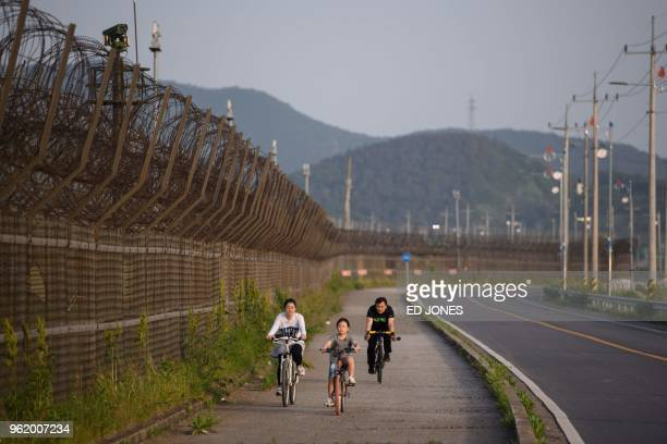 TOPSHOT A family ride bicycles along a barbed wire fence of the Demilitarized Zone separating North and South Korea on Ganghwa island on May 24 2018...