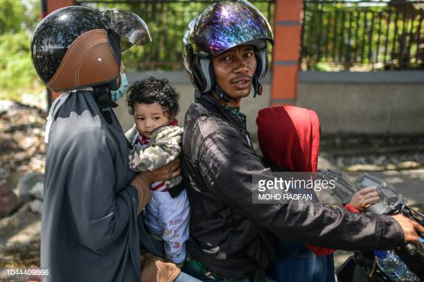 A family rides a motorcycle as they wait for updates on the status of their relatives in Perumnas Balaroa village in Palu Indonesia's Central...
