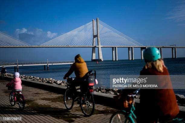 Family rides bicycles near Vasco da Gama bridge at Parque Tejo in Lisbon on January 22, 2021. - Portugal has closed schools for two weeks in a bid to...