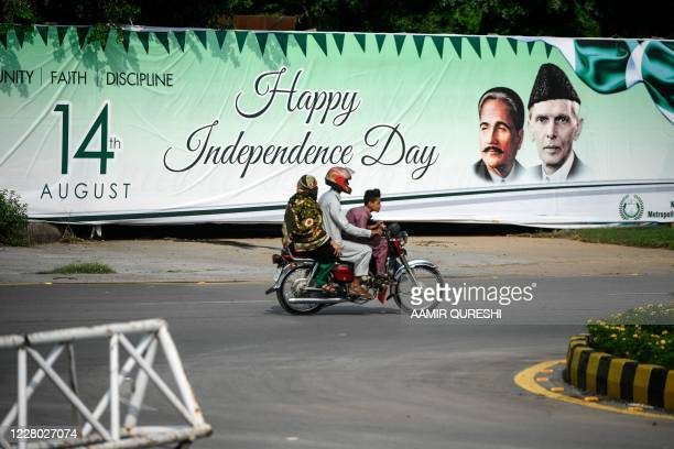Family rides on a bike past a banner reading 'Happy Independence Day' with images of founder leader Mohammad Ali Jinnah and national poet Allama...