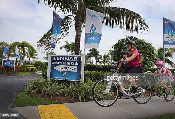 A family rides their bike past a Lennar Corp sign as the company reports that it's thirdquarter net income ending on August 31st rose to $871 million...