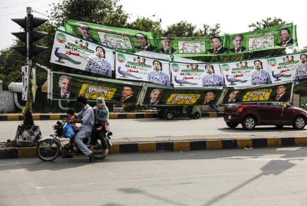 A family riding a motorcycle wait at a signal light in front of campaign banners for Pakistan Muslim LeagueNawaz top and bottom and Pakistan Qoumi...
