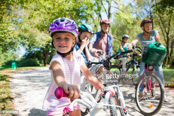 family riding bicycle in park - cycling helmet stock pictures, royalty-free photos & images
