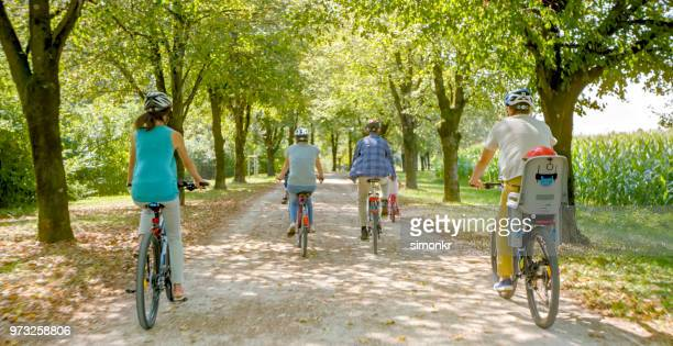 family riding bicycle in park - cycling helmet stock photos and pictures
