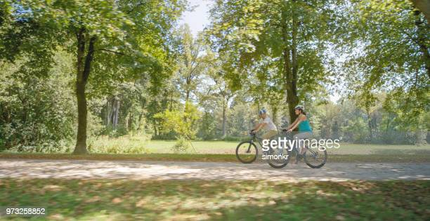family riding bicycle in park - natural parkland stock pictures, royalty-free photos & images