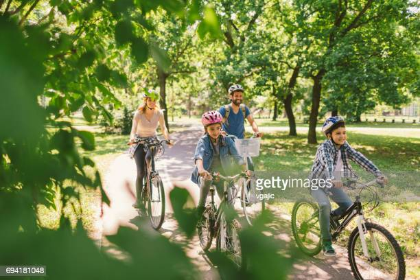 family riding bicycle - riding stock pictures, royalty-free photos & images