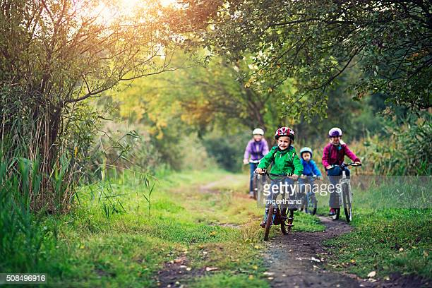 family riding bicycles in beautiful nature - cycling stock pictures, royalty-free photos & images