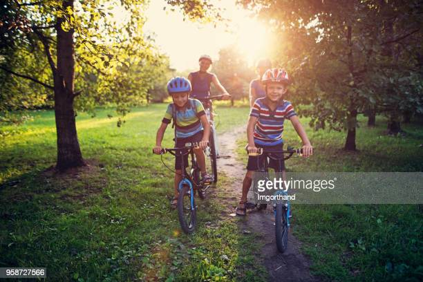 family riding bicycles in park - bicycle stock pictures, royalty-free photos & images