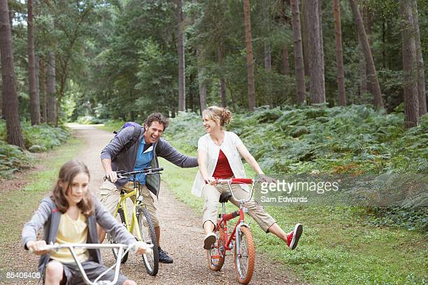 family riding bicycles in woods - 40 49 jaar stockfoto's en -beelden