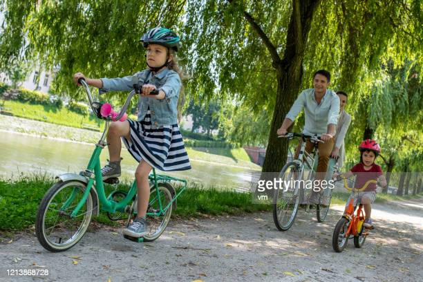 family riding bicycles on a river bank - riverbank stock pictures, royalty-free photos & images